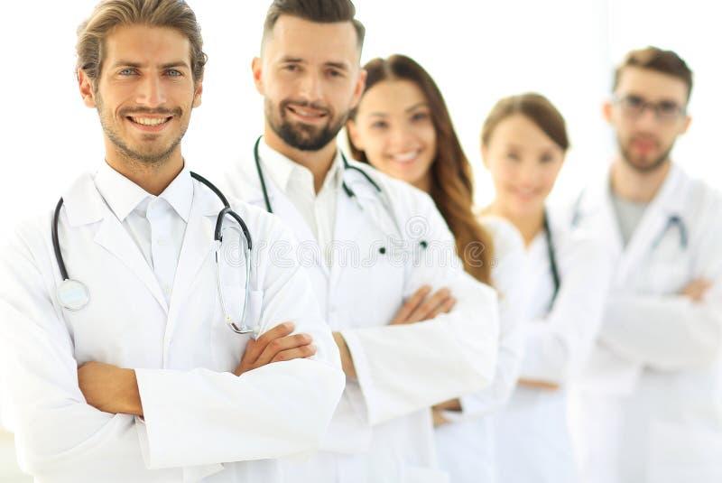 O retrato da equipa médica que está com braços cruzou-se no hospital fotografia de stock royalty free