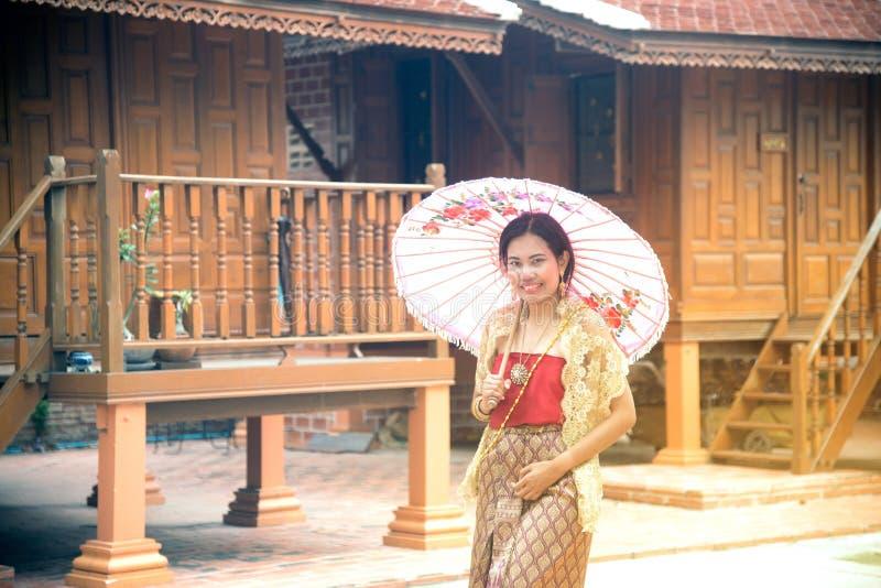 O retrato da fêmea asiática em vestidos tradicionais levanta na casa tailandesa fotos de stock