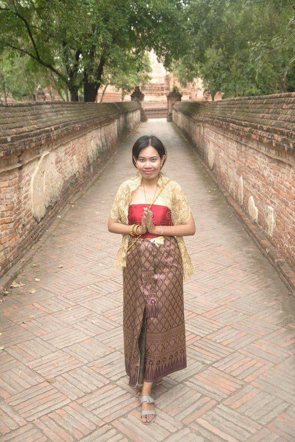 O retrato da fêmea asiática em vestidos tradicionais levanta a posição no templo antigo fotos de stock