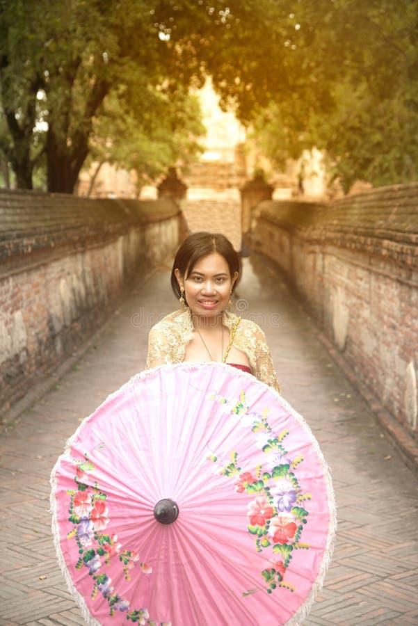 O retrato da fêmea asiática em vestidos tradicionais levanta um guarda-chuva guardando foto de stock royalty free