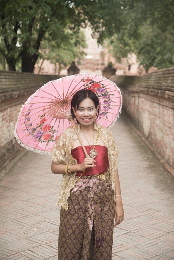 O retrato da fêmea asiática em vestidos tradicionais levanta um guarda-chuva guardando imagem de stock