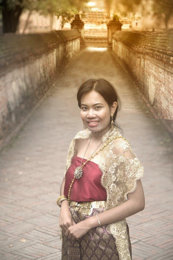 O retrato da fêmea asiática em vestidos tradicionais levanta uma posição no templo antigo foto de stock royalty free