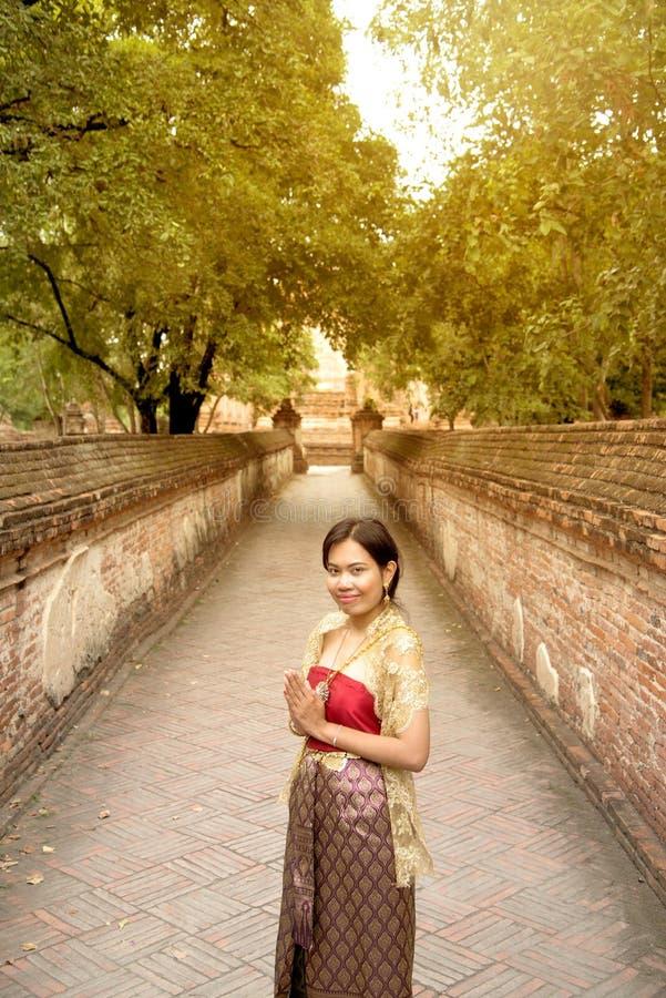 O retrato da fêmea asiática em vestidos tradicionais levanta uma posição no templo antigo fotografia de stock royalty free