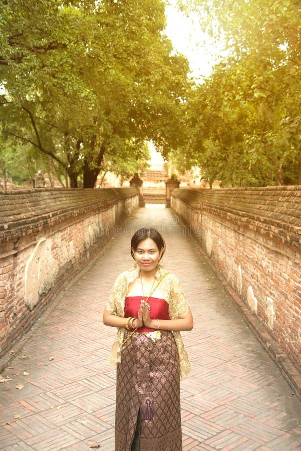 O retrato da fêmea asiática em vestidos tradicionais levanta uma posição no templo antigo imagem de stock