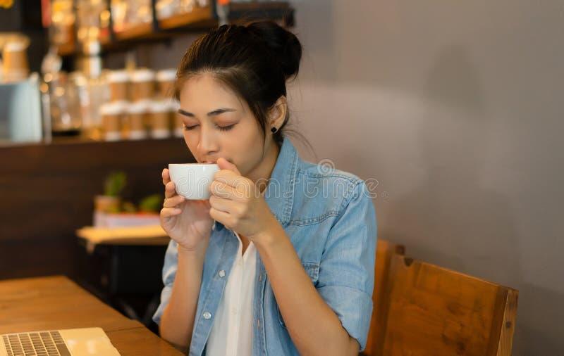 O retrato da fêmea lindo asiática nova com seus olhos fechou a apreciação do cheiro do café delicioso fresco na cafetaria imagem de stock