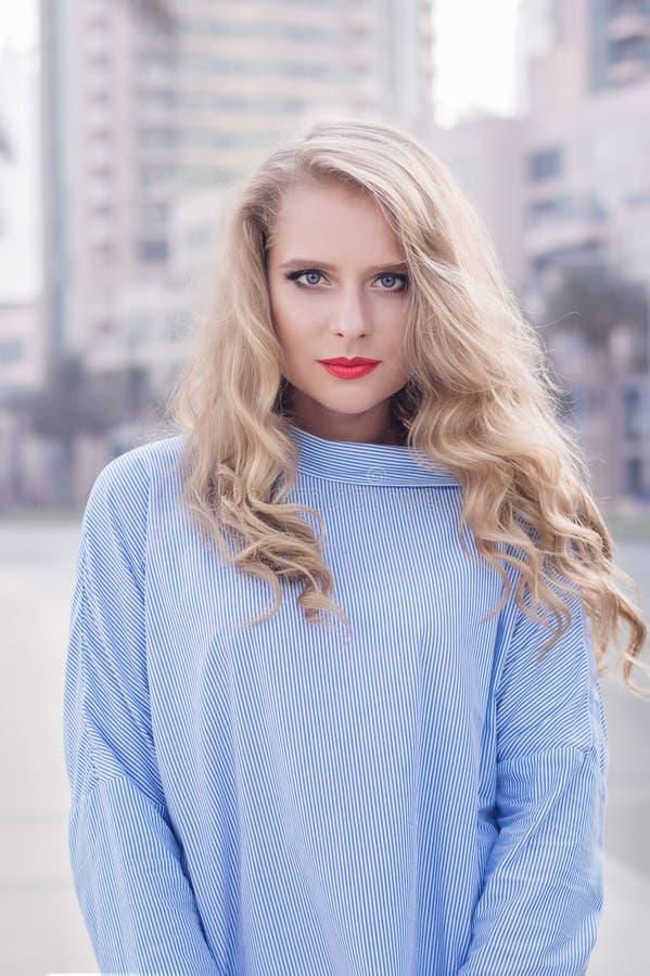 O retrato da fêmea loura nova com na moda compõe com os bordos vermelhos fotografia de stock