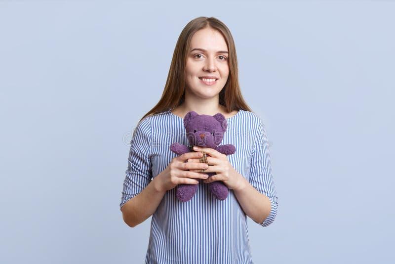 O retrato da fêmea nova bonita com cabelo reto longo guarda o urso de peluche nas mãos, demonstra seu brinquedo favorito, agains  imagens de stock