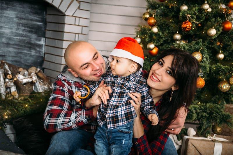 O retrato da família do Natal do sorriso feliz novo parents o jogo com a criança pequena no chapéu vermelho de Santa perto da árv foto de stock royalty free