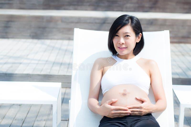 O retrato da jovem mulher asiática grávida bonita relaxa no parque, menina com a barriga que senta-se na piscina para o bem-estar fotografia de stock royalty free