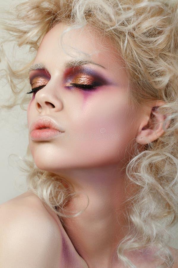 O retrato da jovem mulher com cabelo encaracolado louro e a forma fazem-u imagens de stock