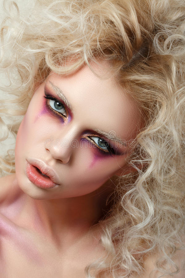 O retrato da jovem mulher com cabelo encaracolado louro e a forma fazem-u foto de stock
