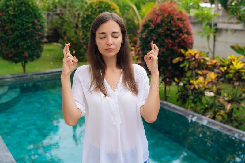 O retrato da jovem mulher com olhos próximos, os dedos transversais com esperança algo vem fundo verdadeiro da associação imagem de stock