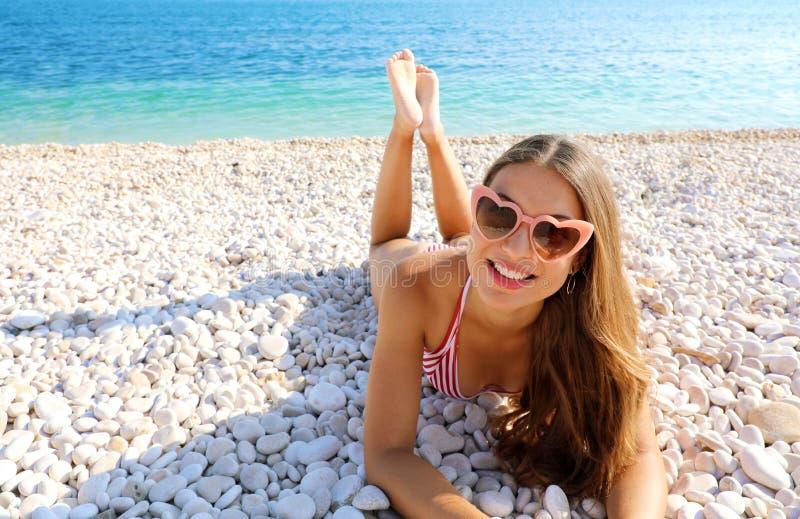 O retrato da jovem mulher com os óculos de sol do coração que encontram-se em seixos encalha Conceito das f?rias de ver?o fotos de stock royalty free