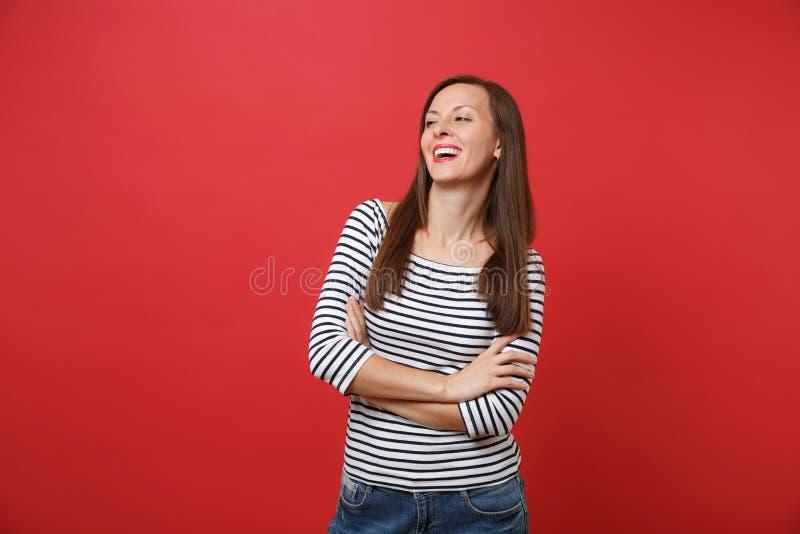 O retrato da jovem mulher de riso em roupa listrada que está, olhando de lado guardando as mãos dobrou-se isolado no vermelho bri fotografia de stock