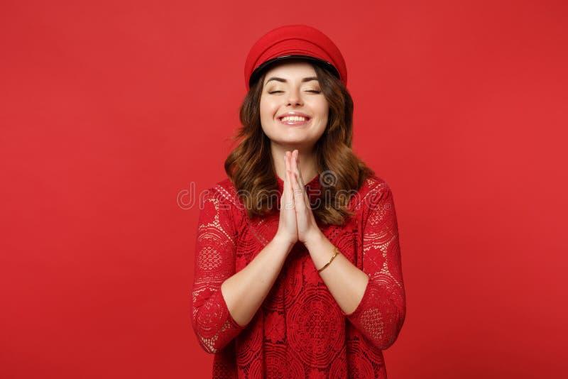 O retrato da jovem mulher de sorriso no vestido do laço, tampão que mantém os olhos fechados, guardando as mãos dobrou rezar em b imagem de stock royalty free