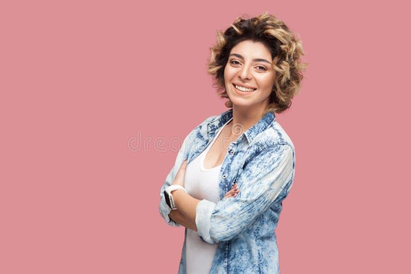 O retrato da jovem mulher feliz bem sucedida bonita com penteado encaracolado na posição azul ocasional da camisa cruzou os braço fotografia de stock royalty free