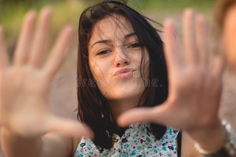 O retrato da jovem mulher pôs suas mãos à câmera verão, luz brilhante fotos de stock royalty free