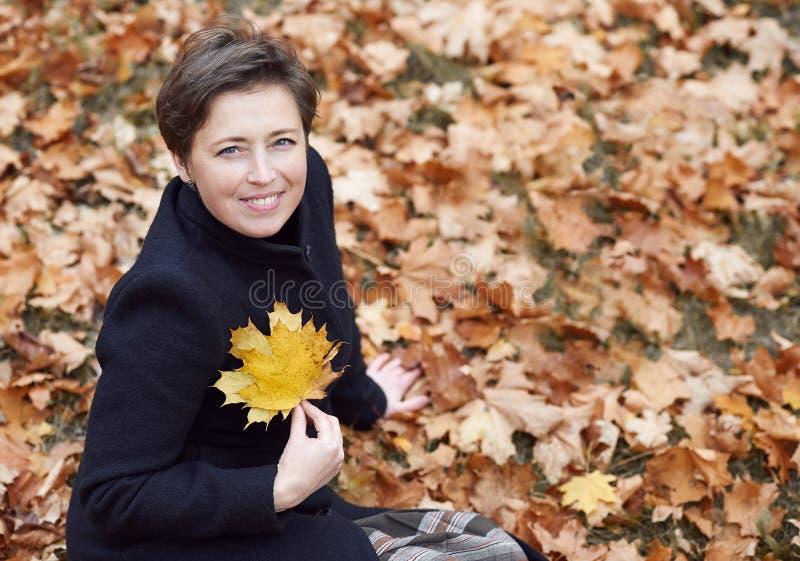 O retrato da jovem mulher, sentando-se no fundo amarelo das folhas, vestiu-se no revestimento preto, estação do outono, parque da foto de stock