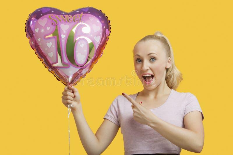 O retrato da jovem mulher surpreendida que guarda o coração deu forma ao balão do aniversário sobre o fundo amarelo imagens de stock