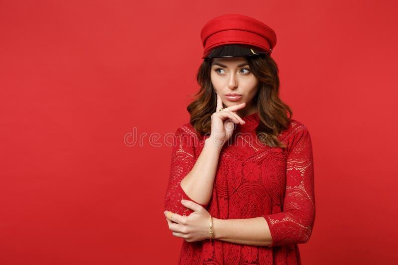 O retrato da jovem mulher thinkful no vestido do laço, tampão que olha de lado, colocou o suporte da mão sobre o queixo no vermel foto de stock