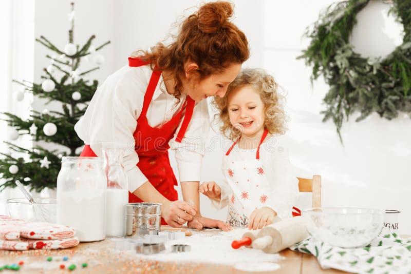 O retrato da mãe alegre e a filha vestem aventais, estão na cozinha, preparam a torta deliciosa para a tabela do ano novo fotografia de stock