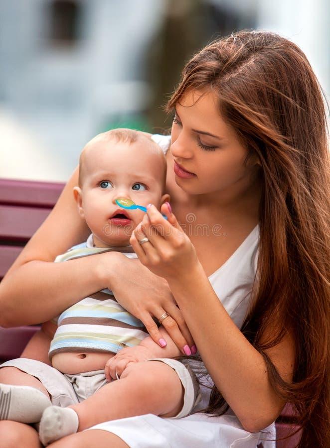 O retrato da mãe bonita feliz alimenta-lhe o verão do bebê fora no parque imagem de stock royalty free