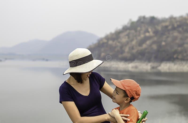 O retrato da mãe e o filho são montanhas e água de sorriso do fundo na represa de Krasiew, Supanburi Tailândia imagens de stock royalty free