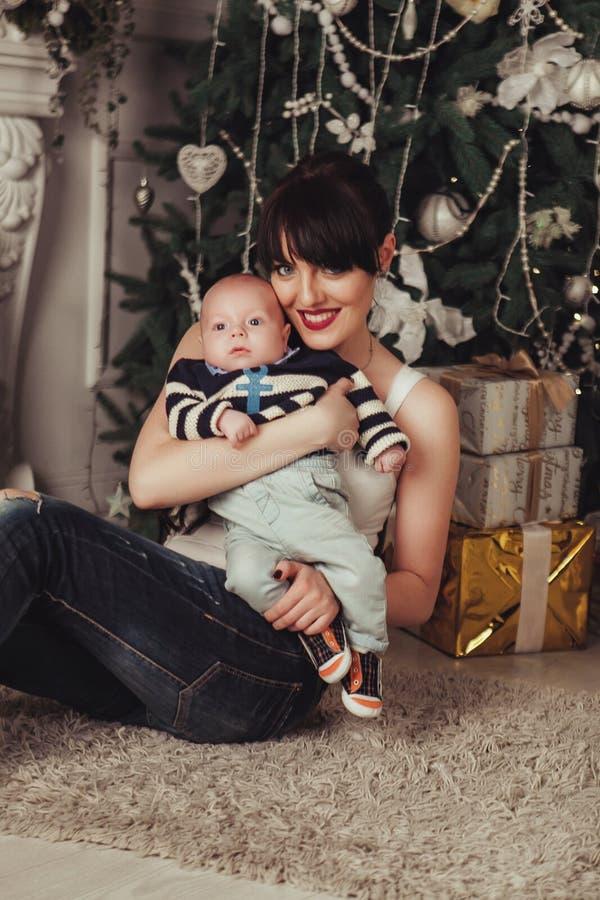 O retrato da mãe feliz e do bebê pequeno próximo decorou a árvore de Natal com presentes foto de stock