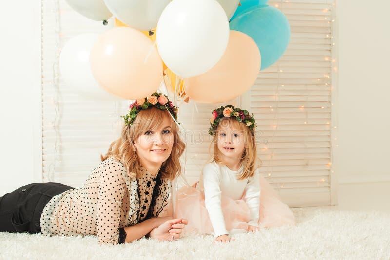 O retrato da mãe feliz e a filha com flor envolvem-se em sua cabeça fotos de stock