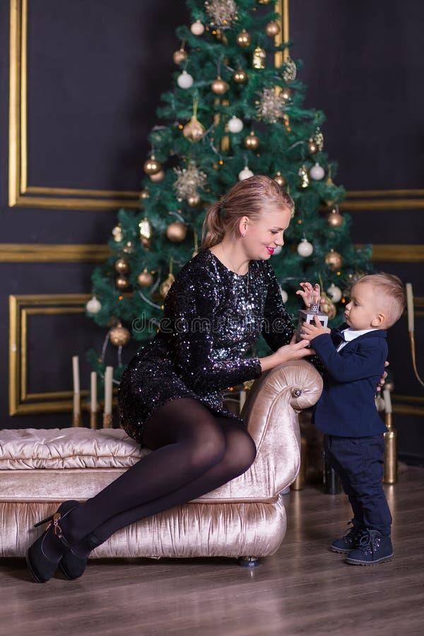 O retrato da mãe feliz e o bebê adorável comemoram o Natal Feriados do ` s do ano novo Criança com a mamã no r festiva decorado imagens de stock royalty free