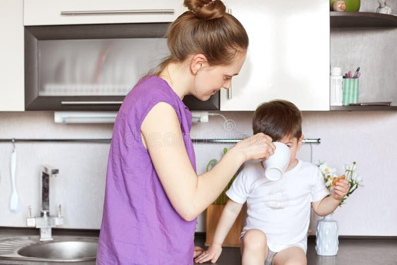O retrato da mãe nova dá a bebida a seu filho pequeno que se senta na mobília da cozinha, toma da criança pequena, sendo ocupado  fotos de stock royalty free