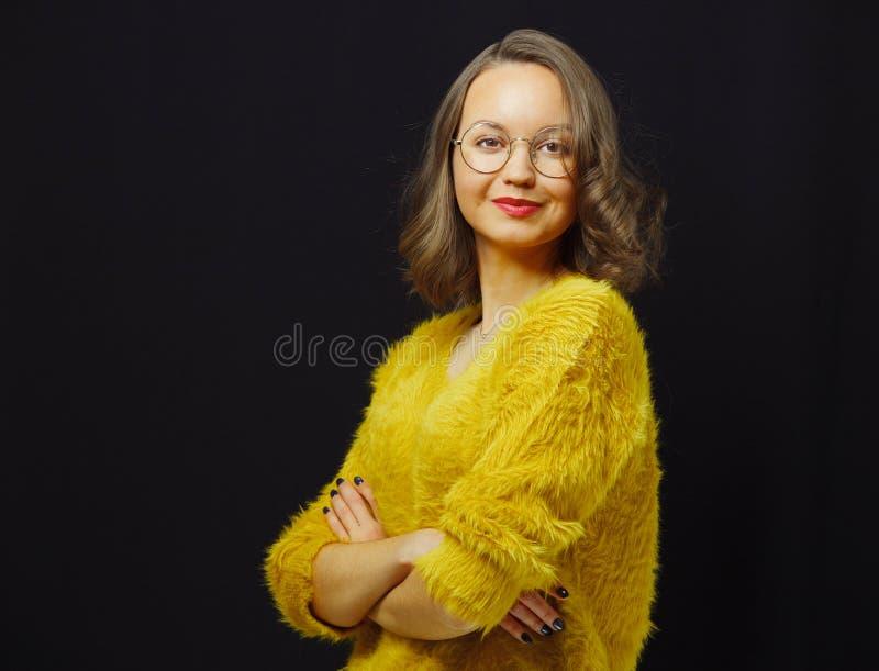 O retrato da menina étnica caucasiano bonita em espetáculos redondos e da camiseta amarela no preto isolou o fundo imagens de stock