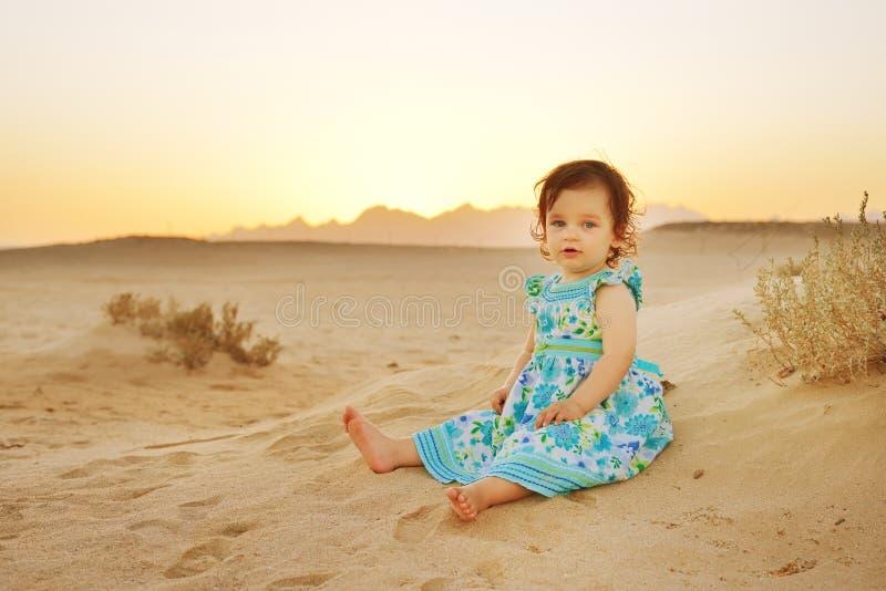 O retrato da menina adorável em férias da praia weared o vestido azul bonito Bebê que senta-se na areia no tempo do por do sol fotos de stock royalty free