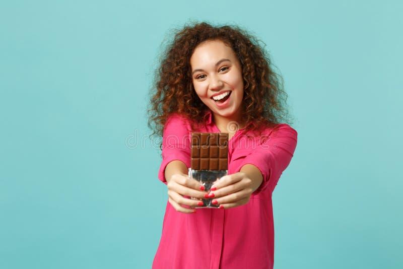O retrato da menina africana bonita feliz na roupa ocasional mantém a barra de chocolate disponivel isolada na parede azul de tur imagem de stock
