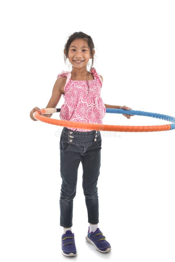 O retrato da menina asiática pequena feliz da criança que joga o hulahoop está ligada foto de stock