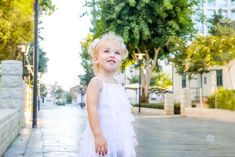 O retrato da menina blondy emocional pequena bonito da criança nas bolhas de jogo e de travamento brancas do vestido de sabão dur foto de stock