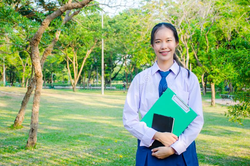 O retrato da menina bonita adolescente uniforme do estudante tailandês da High School feliz e para relaxar guarda cadernos em sua imagem de stock