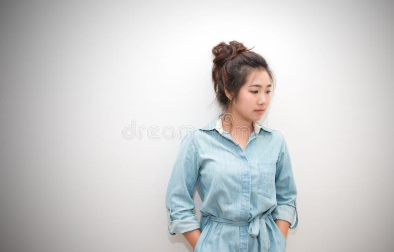 O retrato da menina bonita de Ásia que levanta as mãos em uns bolsos veste-se imagem de stock royalty free