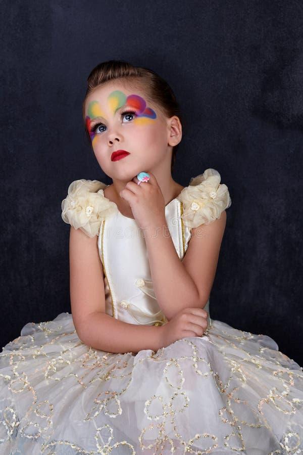 O retrato da menina bonita pensa nos bordos vermelhos do vestido branco com a cara pintada no fundo escuro foto de stock