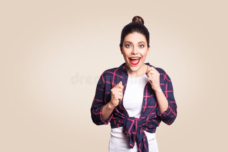 O retrato da menina bonita que tem o vencimento e expressão facial feliz, exclamando com alegria, mantendo as mãos nos punhos e a fotos de stock