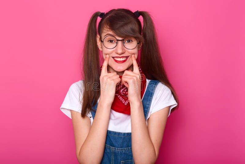 O retrato da menina bonito com cabelo longo, veste a camisa de t, os macacões da sarja de Nimes e o bandana no pescoço Estudante  fotos de stock