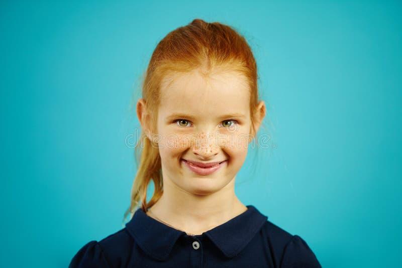 O retrato da menina bonito com sardas e cabelo vermelho, sorrindo sinceramente, tem características faciais agradáveis, expressa  imagens de stock