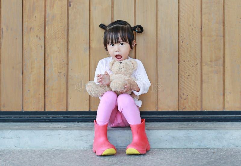 O retrato da menina bonito senta-se e abra?ando Teddy Bear contra a parede de madeira da prancha fotografia de stock
