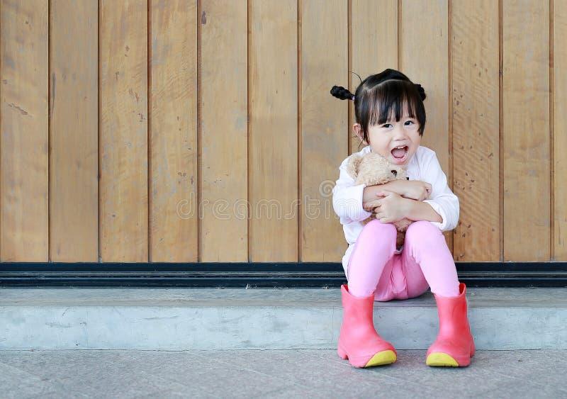 O retrato da menina bonito senta-se e abra?ando Teddy Bear contra a parede de madeira da prancha fotos de stock