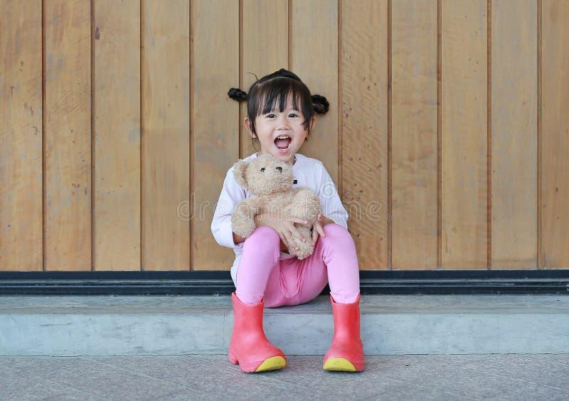 O retrato da menina bonito senta-se e abra?ando Teddy Bear contra a parede de madeira da prancha foto de stock royalty free