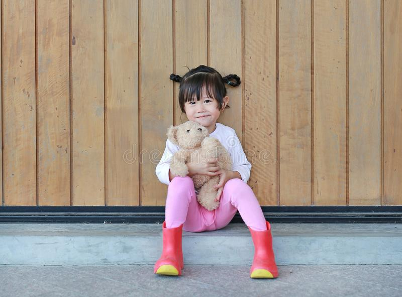 O retrato da menina bonito senta-se e abra?ando Teddy Bear contra a parede de madeira da prancha foto de stock