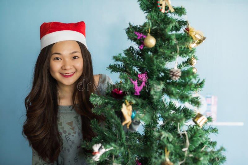 O retrato da menina chinesa asiática feliz com chapéu de Santa Claus comemora o Natal perto da árvore do xmas para apreciar 2018  fotos de stock