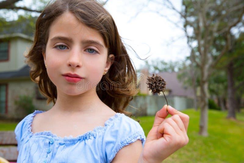 O retrato da menina com sweetgum cravou o fruto no parque foto de stock royalty free