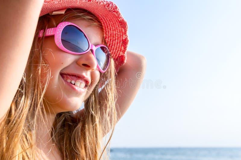 O retrato da menina da criança com chapéu do verão e os óculos de sol relaxam em s imagem de stock