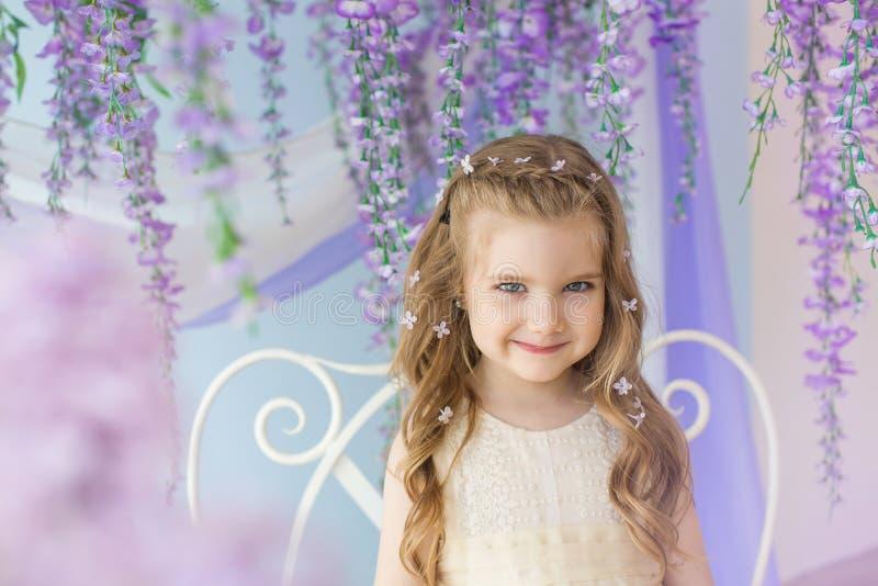 O retrato da menina de sorriso em um vestido amarelo em uma sala decorou lilás imagem de stock